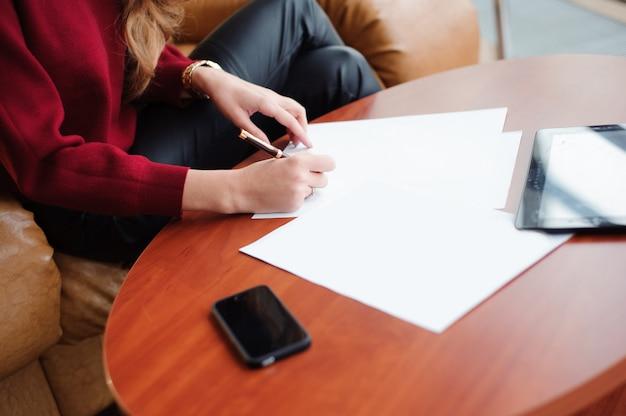 라운지에서 서류와 함께 작동하는 젊은 비즈니스 여자.
