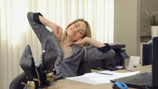 Молодой бизнес женщина, зевая на современный офисный стол перед ноутбуком.