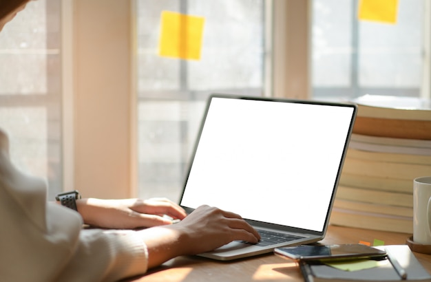 Young business women are using blank screen laptop with office equipment in modern office.