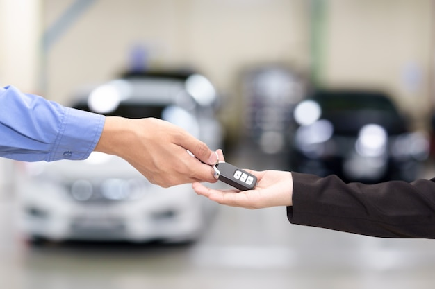 Young business women giving a key car in font of car.