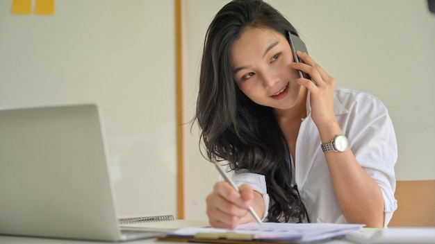 電話で若いビジネスウーマンがオフィスでコーディネートします。