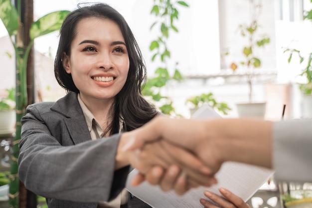 Молодые деловые женщины пожимают друг другу руки в кафе