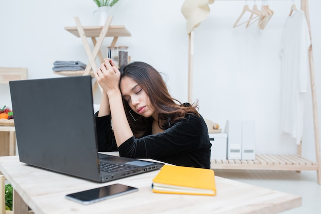 젊은 비즈니스 여성들은 늦게까지 일한 후 테이블에서 잠을 자고, 밤 늦게까지 일하는 비즈니스 개념