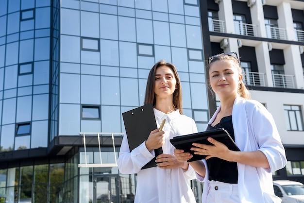 ビジネスセンターの外でポーズをとってタブレットとクリップボードを持つ若いビジネス女性