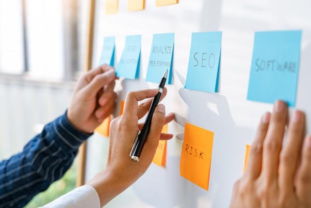 Молодые бизнес-работники, размещающие стикеры с липкими заметками, напоминают о творческом мозговом штурме у коллеги в современном пространстве совместной работы