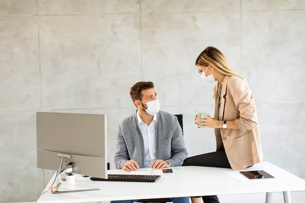 若いビジネスワーカーは、オフィスで健康を守り、世話をするためにマスクを着用しています