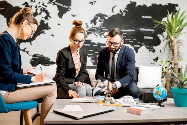 背景に世界地図と旅行代理店のオフィスに座っているエージェントと一緒に旅行を選ぶ若いビジネスカップル