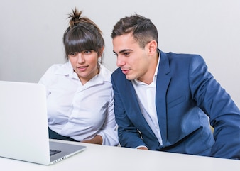 Young businessman and businesswoman looking at laptop