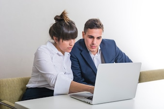 Young businessman and businesswoman using laptop