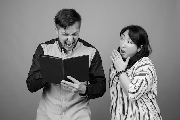 Молодой бизнесмен и зрелая японская бизнес-леди вместе против серого в черно-белом