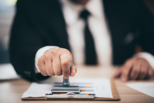 Штамповка одобрения молодого бизнесмена на бумажном деловом контракте