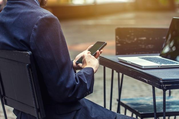 Молодой бизнесмен использует смартфоны для связи с клиентами.