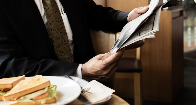 Young businessman in a black jacket reading a newspaper in a cafe