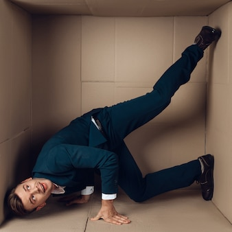 Young businessman in black suit in cardboard box.