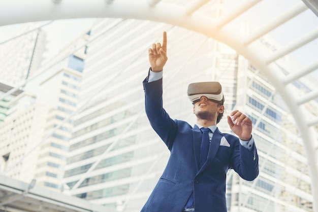 5b564811302a Young businessman in black suit wearing virtual reality goggles.