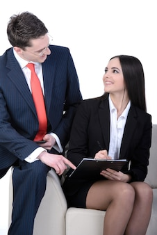 Young businessman and business woman sitting on a sofa.