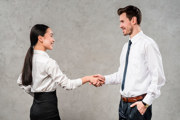 Young businessman and businesswoman shaking each other's hand against grey wall