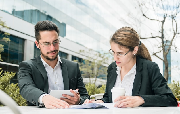 Young businessman and businesswoman sitting at outdoor caf� looking at document