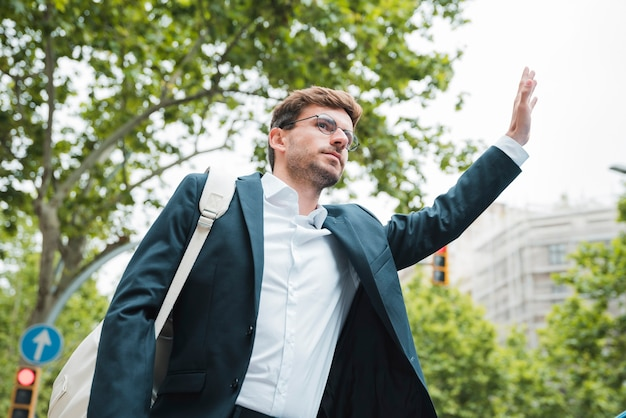 Young businessman carrying white backpack on his shoulder hitchhiking