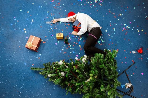 Young businessman celebrating christmas in office sleeping on floor.