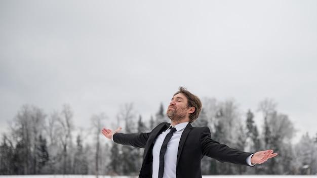 Молодой бизнесмен празднует успех, стоя снаружи в снежной природе с широко раскинутыми руками.