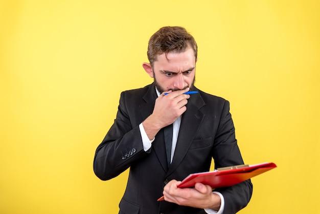 Молодой бизнесмен проверяет статистику и пишет на бланке на желтом