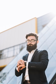 Young businessman checking time standing against office building