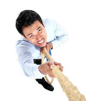 Молодой бизнесмен взбираясь вверх используя веревку