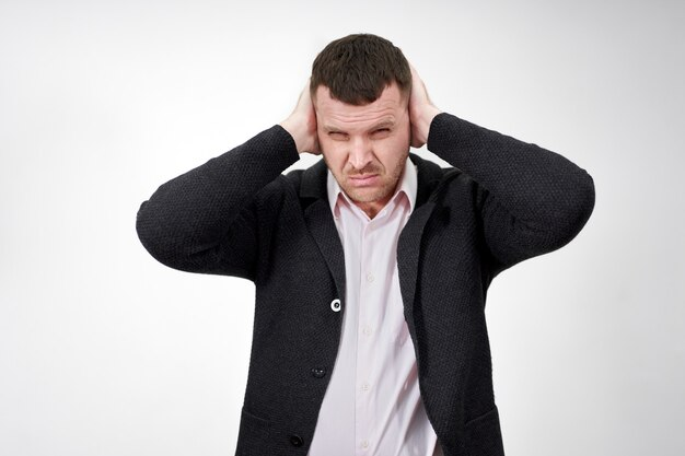 Young businessman closing ears with hands on head