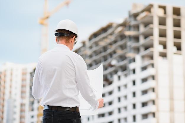 Молодой предприниматель, инженер строительной площадки, крупным планом.