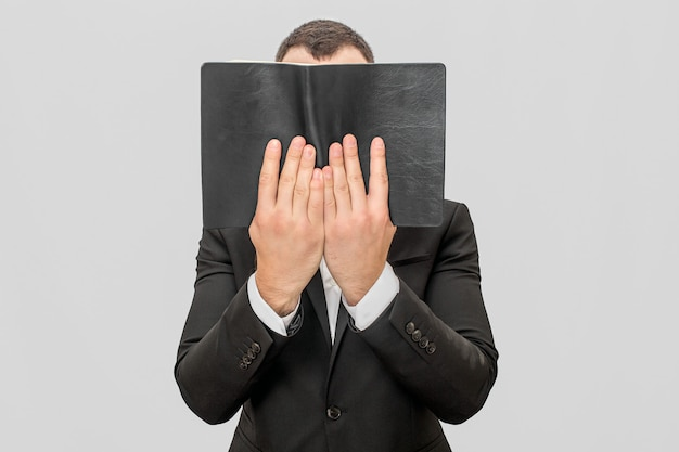 Young businessman coveres face with book in dark cover. he hold it with both hands. guy weas suit.