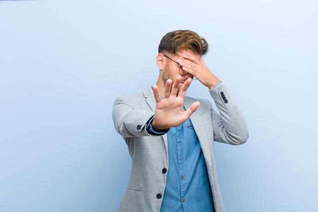 青年実業家の手で顔を覆って、他の手を前に置いてカメラを停止し、写真や写真を青に対して拒否
