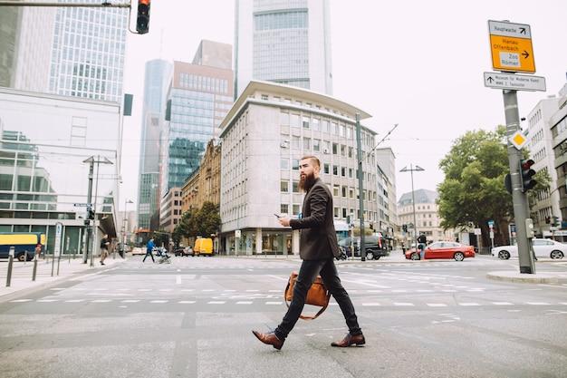 若いビジネスマンは美しい街で道路を横断します