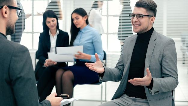 Молодой бизнесмен обсуждает с коллегой свои идеи. рабочие будни в офисе