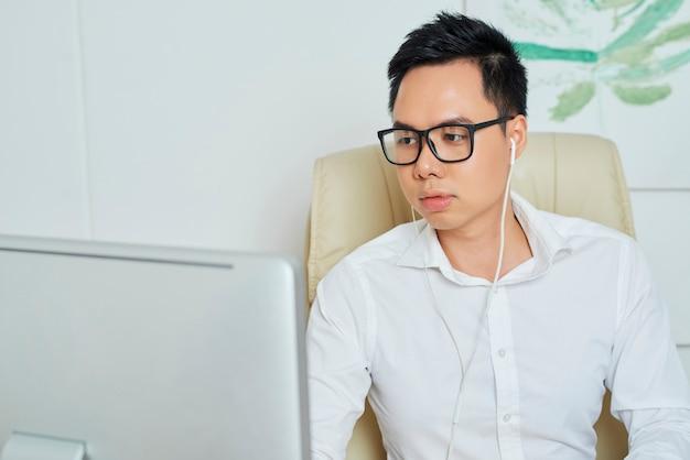 Young businessman in earphones