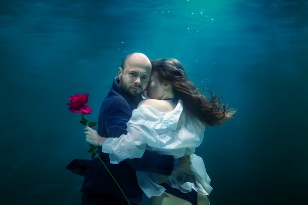 Young businessman embraces his woman, gives rose, kisses beloved, underwater. emotional happy couple in pond. concept romantic date, surprise and commitment to development of relations. copy space