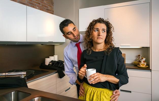 부엌에서 커피 한 잔을 들고 화난 곱슬머리 여성을 껴안은 젊은 사업가