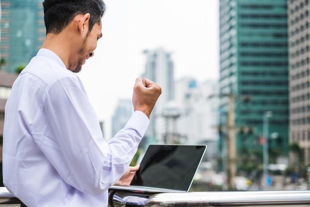 흥분된 젊은 사업가가 손을 들고 도시에서 노트북과 함께 기뻐하고 웃고 있습니다.