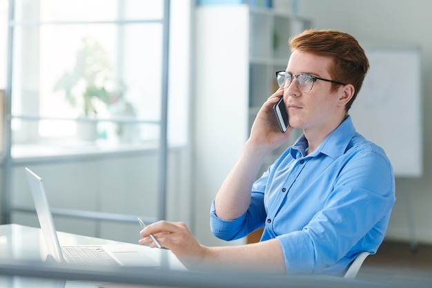 Young businessman in eyeglasses and blue shirt consulting client by smartphone while working in office