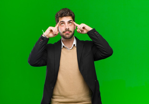 Young businessman feeling confused or doubting, concentrating on an idea, thinking hard, looking to copy space on side against green wall