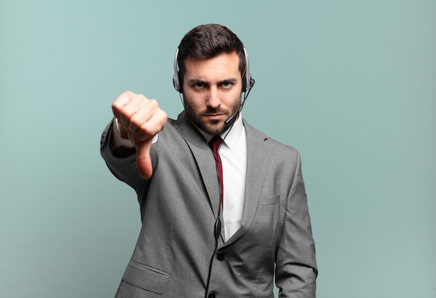 Young businessman feeling cross, angry, annoyed, disappointed or displeased, showing thumbs down with a serious look telemarketing concept