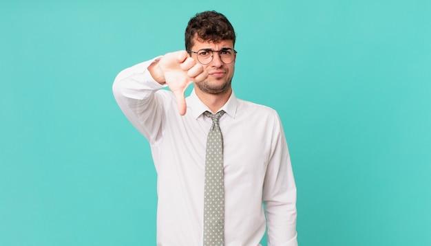 젊은 사업가는 십자가, 화난, 짜증, 실망 또는 불쾌감을 느끼며 진지한 표정으로 엄지손가락을 아래로 내보입니다.