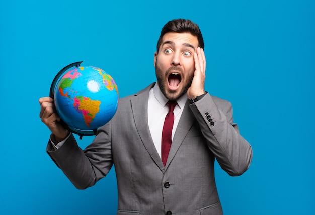 젊은 사업가 행복, 흥분 및 놀란 느낌, 세계 세계지도를 들고 얼굴에 양손으로 측면을 찾고