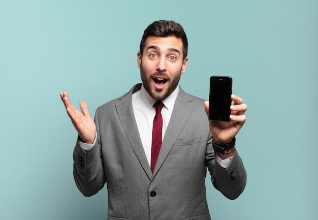幸せ、驚き、陽気を感じ、前向きな姿勢で笑い、解決策やアイデアを実現し、彼の電話画面を表示する青年実業家