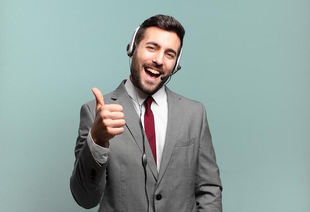 誇り高く、気楽で、自信を持って幸せを感じ、テレマーケティングのコンセプトを高く評価してポジティブに微笑む若いビジネスマン