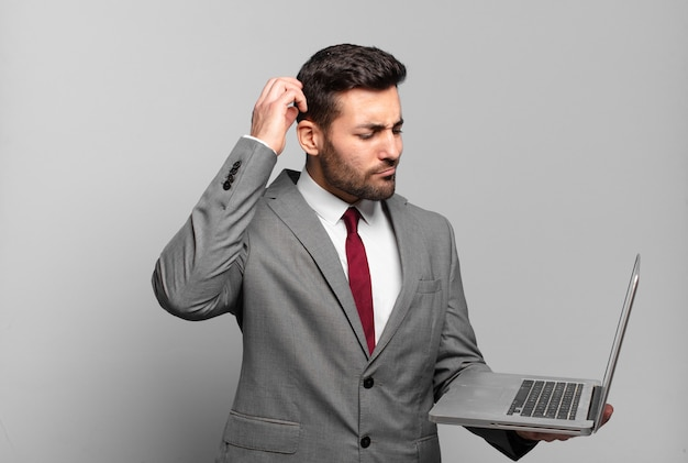 Young businessman feeling puzzled and confused, scratching head and looking to the side and holding a laptop