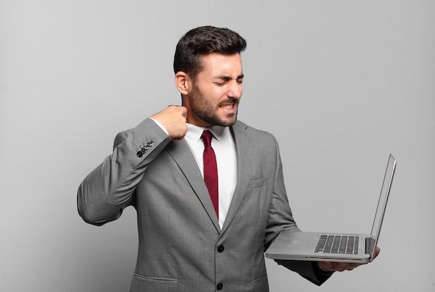 Молодой бизнесмен чувствует стресс, тревогу, усталость и разочарование, дергает за шею рубашки, выглядит разочарованным из-за проблемы и держит ноутбук