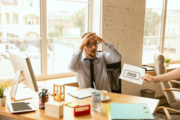 若いビジネスマンは解雇され、動揺しているように見えます。彼のオフィスの持ち物を梱包し、新しい労働者のために職場を離れなければなりません。職業、ストレス、失業、新しい生き方、またはキャリアの終わりの問題。