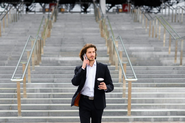 Young businessman in full suit standing outdoors