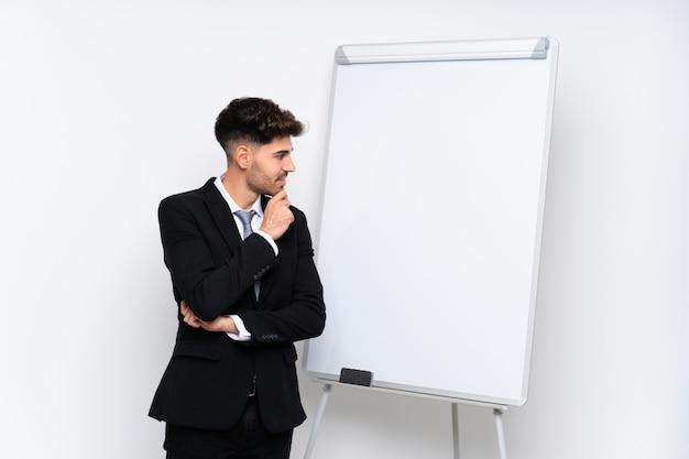 側を見てホワイトボードにプレゼンテーションを行う青年実業家